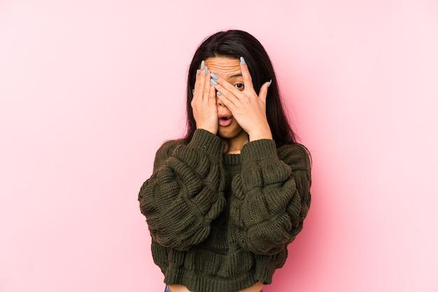 Jeune femme chinoise isolée sur fond rose clignote entre les doigts effrayés et nerveux.