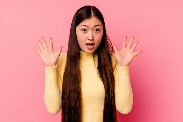 Jeune femme chinoise isolée sur fond rose criant vers le ciel, levant les yeux, frustrée.