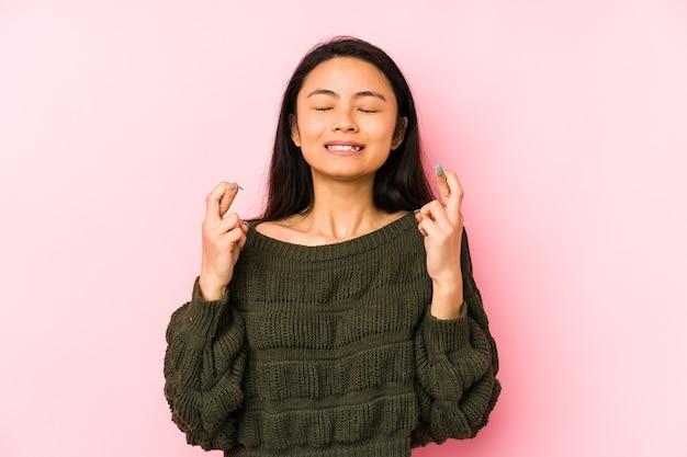 Jeune femme chinoise isolée sur fond rose, croisant les doigts pour avoir de la chance