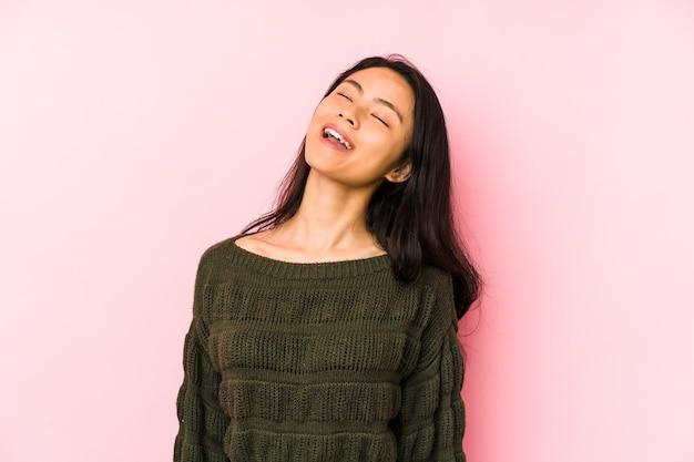 Jeune femme chinoise isolée sur fond rose détendu et heureux en riant, cou tendu montrant les dents.