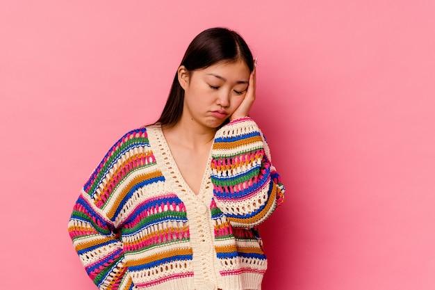 Jeune femme chinoise isolée sur fond rose qui s'ennuie, fatiguée et a besoin d'une journée de détente.