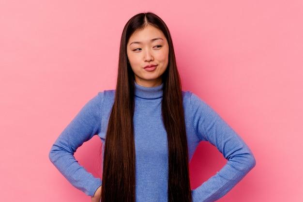 Jeune femme chinoise isolée sur fond rose, rêvant d'atteindre les objectifs et les buts