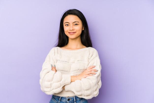 Jeune femme chinoise isolée sur fond violet qui se sent confiant, croisant les bras avec détermination.