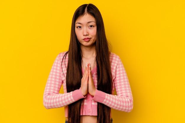 Jeune femme chinoise isolée sur jaune priant, montrant la dévotion, personne religieuse à la recherche d'inspiration divine.