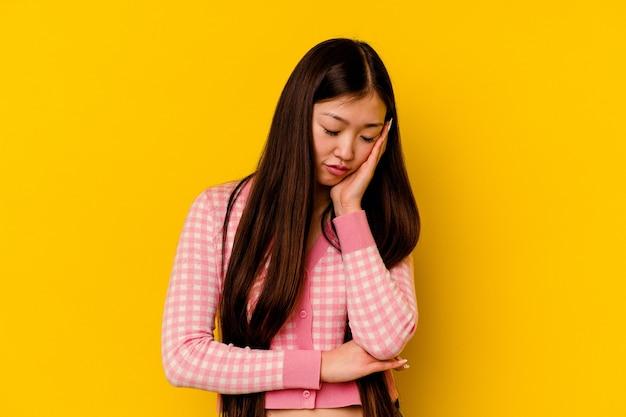 Jeune femme chinoise isolée sur jaune qui s'ennuie, fatiguée et a besoin d'une journée de détente.