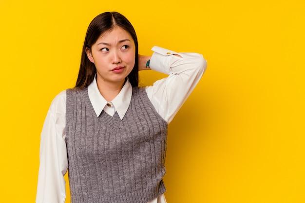 Jeune femme chinoise isolée sur jaune touchant l'arrière de la tête, pensant et faisant un choix.
