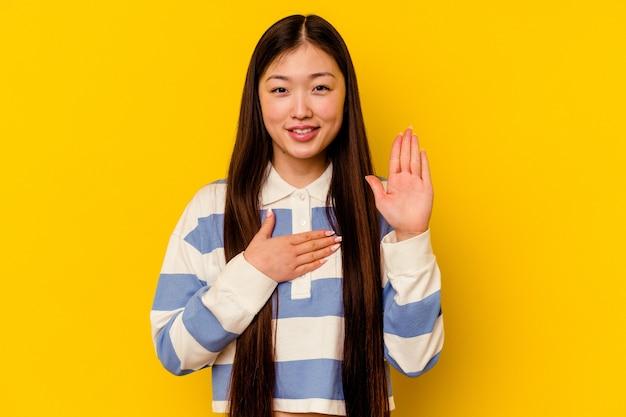 Jeune femme chinoise isolée sur mur jaune en prêtant serment, mettant la main sur la poitrine