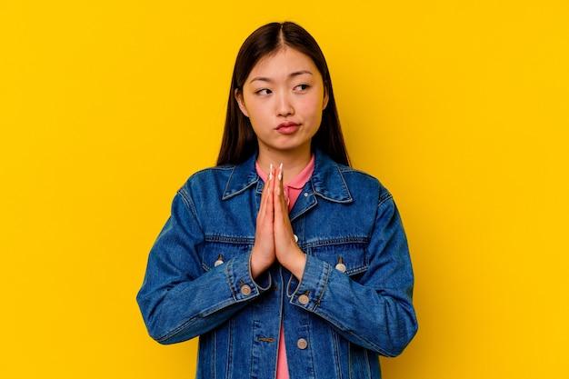 Jeune femme chinoise isolée sur un mur jaune priant, montrant la dévotion, personne religieuse à la recherche d'inspiration divine