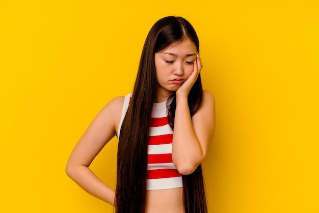 Jeune femme chinoise isolée sur mur jaune qui s'ennuie, fatigué et a besoin d'une journée de détente
