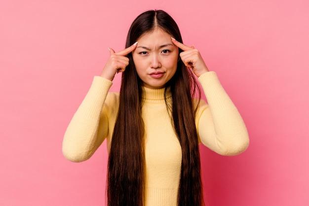 Jeune femme chinoise isolée sur un mur rose concentré sur une tâche, gardant l'index pointant la tête.