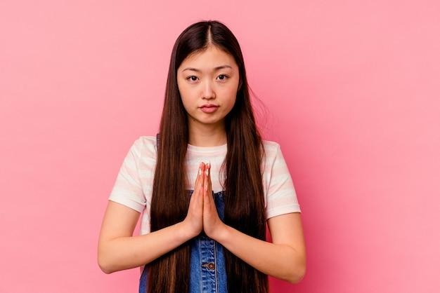 Jeune femme chinoise isolée sur un mur rose priant, montrant la dévotion, personne religieuse à la recherche d'inspiration divine.