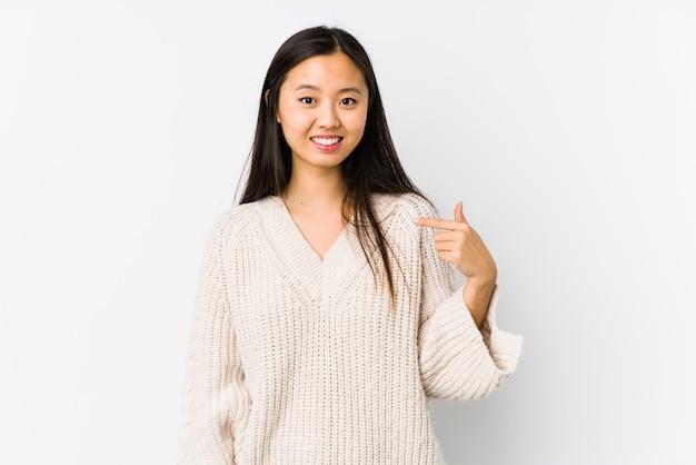 Jeune femme chinoise isolée pointant à la main vers un espace de copie de chemise, fier et confiant