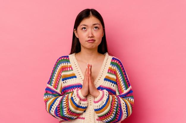 Jeune femme chinoise isolée sur rose tenant par la main en priant près de la bouche, se sent confiant.