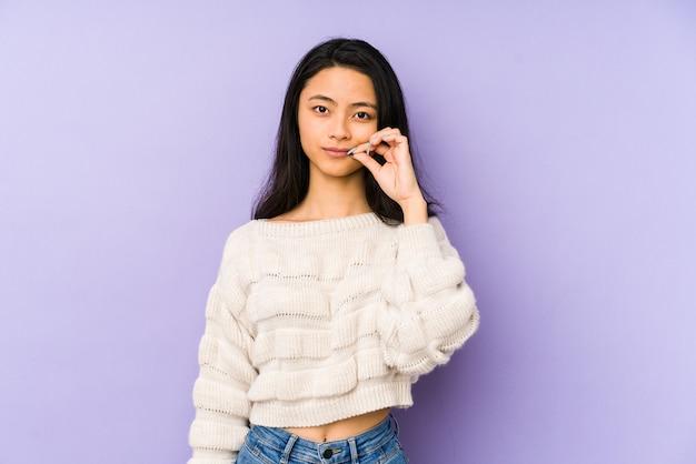 Jeune femme chinoise isolée sur violet avec les doigts sur les lèvres en gardant un secret.