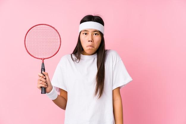 Jeune femme chinoise jouant au badminton sur fond rose hausse les épaules et les yeux ouverts confus.