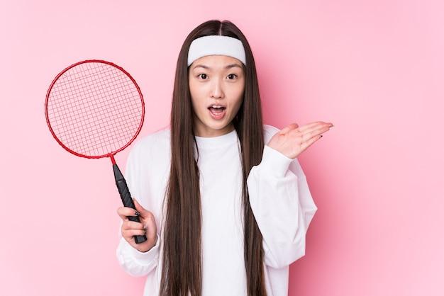Jeune femme chinoise jouant au badminton isolée surprise et choquée.