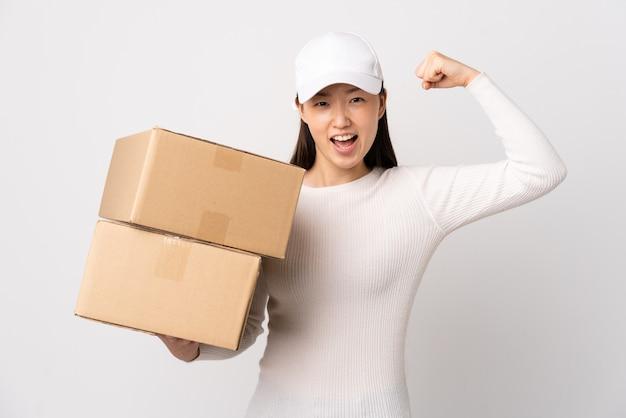 Jeune femme chinoise de livraison sur blanc isolé célébrant une victoire