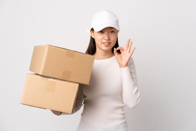 Jeune femme chinoise de livraison sur blanc isolé montrant un signe ok avec les doigts