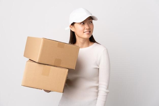 Jeune femme chinoise de livraison sur blanc isolé en riant et en levant
