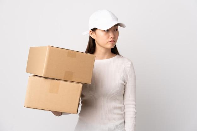 Jeune femme chinoise de livraison sur fond blanc isolé à côté