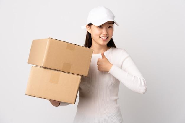 Jeune femme chinoise de livraison sur fond blanc isolé donnant un geste de pouce en l'air