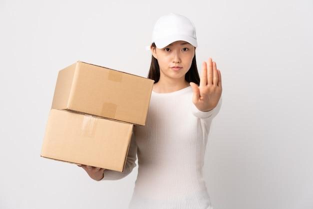 Jeune femme chinoise de livraison sur fond blanc isolé faisant un geste d'arrêt avec sa main