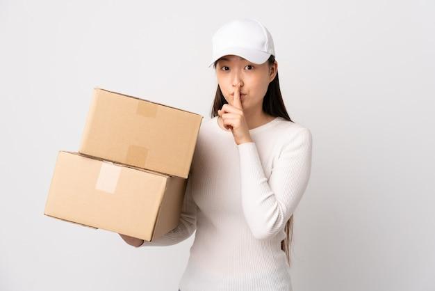Jeune femme chinoise de livraison sur fond blanc isolé faisant un geste de silence