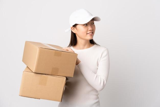 Jeune femme chinoise de livraison sur fond blanc isolé à la recherche sur le côté