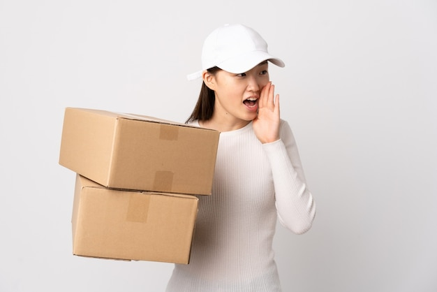 Jeune femme chinoise de livraison isolée en criant avec la bouche grande ouverte