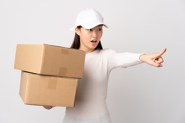 Jeune femme chinoise de livraison isolée doigt pointé sur le côté