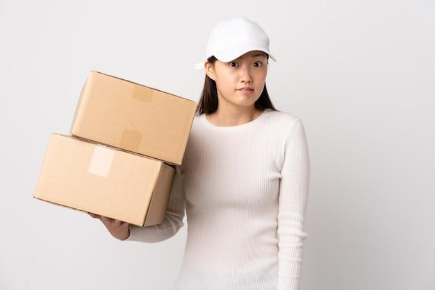 Jeune femme chinoise de livraison sur un mur blanc isolé ayant des doutes et avec l'expression du visage confus