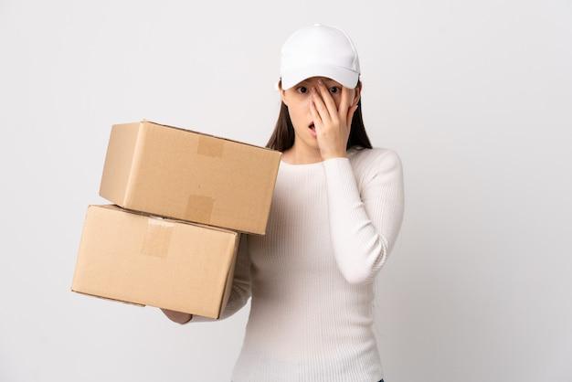Jeune femme chinoise de livraison sur un mur blanc isolé couvrant les yeux et regardant à travers les doigts
