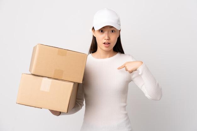 Jeune femme chinoise de livraison sur un mur blanc isolé avec une expression faciale surprise
