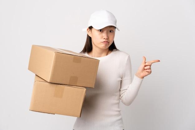 Jeune femme chinoise de livraison sur un mur blanc isolé pointant vers les latéraux ayant des doutes