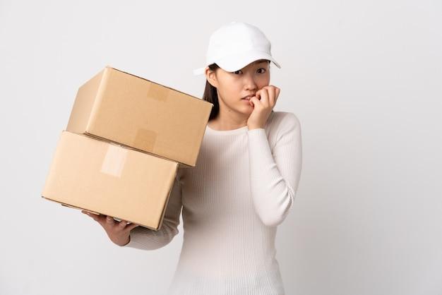 Jeune femme chinoise livraison sur mur blanc nerveux et effrayé