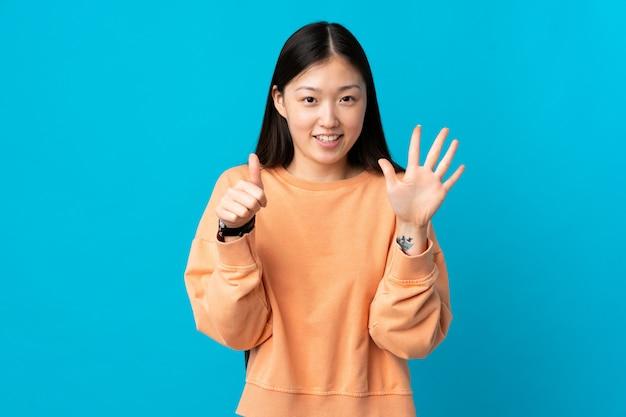 Jeune femme chinoise sur mur bleu isolé comptant six avec les doigts