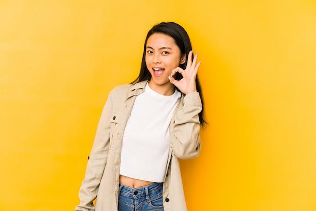 Jeune femme chinoise sur un mur jaune fait un clin d'œil et tient un geste correct avec la main.