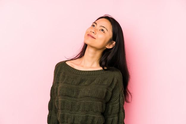 Jeune femme chinoise sur un mur rose rêvant d'atteindre des buts et objectifs