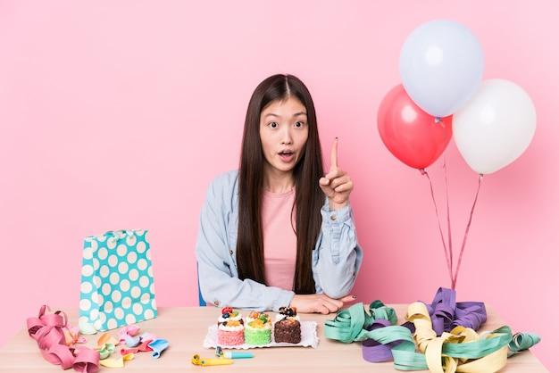 Jeune femme chinoise organisant un anniversaire ayant une bonne idée