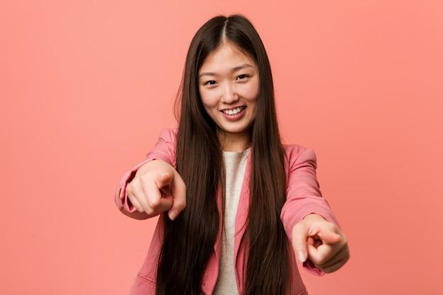 Jeune femme chinoise portant un costume rose souriant sourit joyeux pointant vers l'avant.