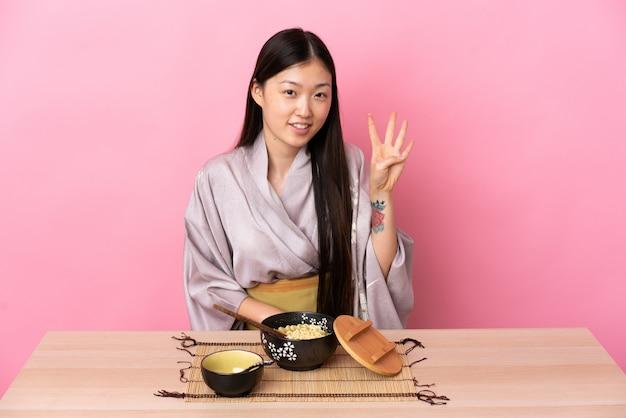Jeune femme chinoise portant un kimono et manger des nouilles heureux et en comptant quatre avec les doigts
