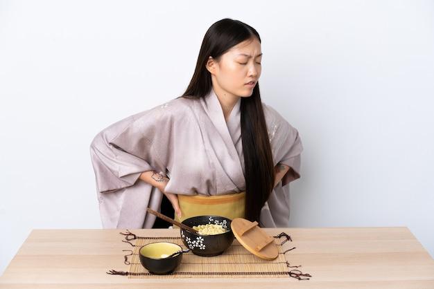 Jeune femme chinoise portant un kimono et manger des nouilles