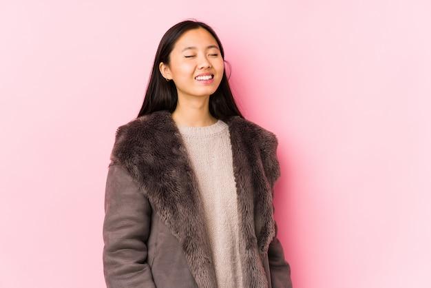 Jeune femme chinoise portant un manteau isolé détendu et heureux de rire, le cou tendu montrant les dents.