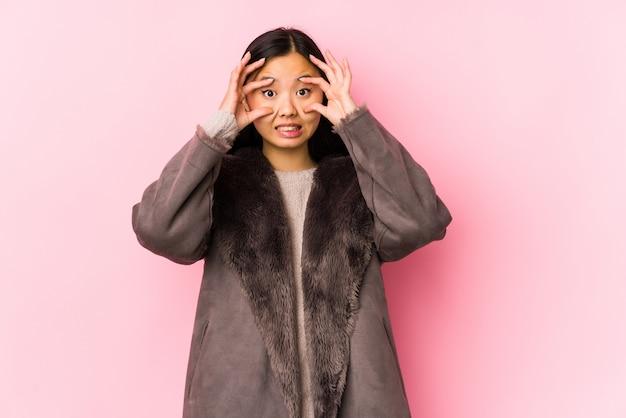 Jeune femme chinoise portant un manteau isolé en gardant les yeux ouverts pour trouver une opportunité de réussite.
