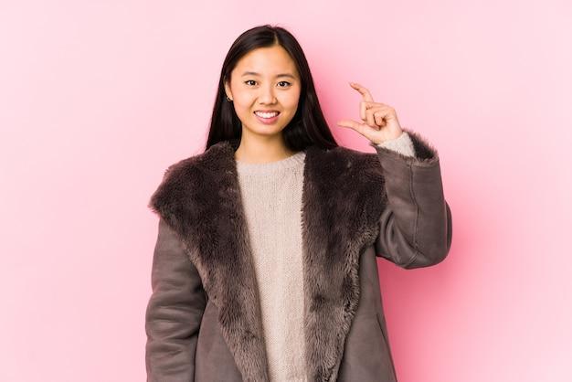 Jeune femme chinoise portant un manteau isolé tenant quelque chose de peu avec l'index, souriant et confiant.