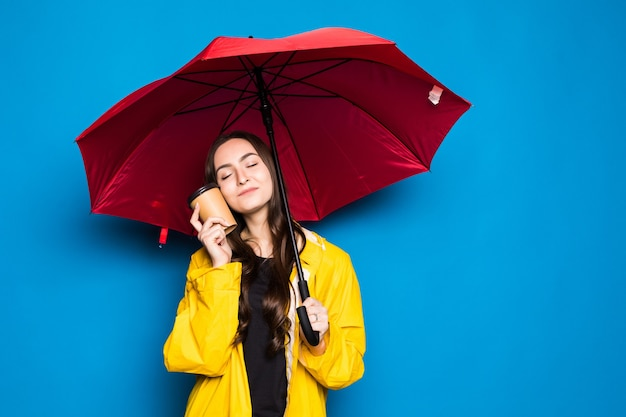 Jeune femme chinoise portant un manteau de pluie tenant un parapluie sur un mur bleu isolé très heureux pointant avec la main et le doigt
