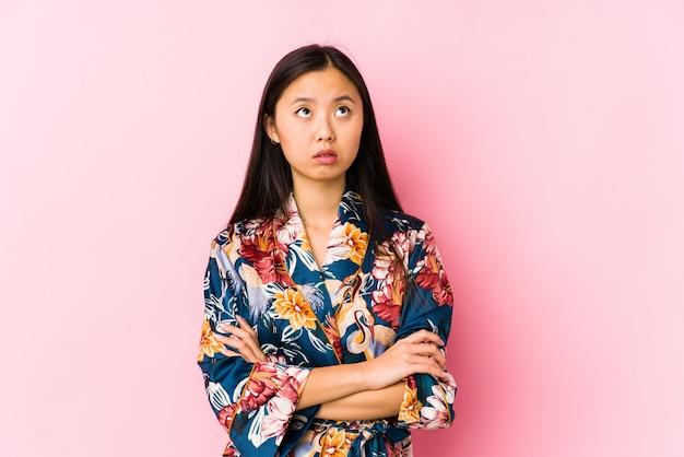 Jeune femme chinoise portant un pyjama kimono isolé fatigué d'une tâche répétitive.