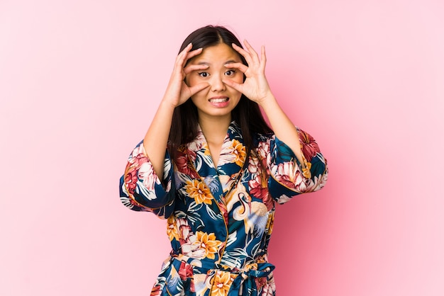Jeune femme chinoise portant un pyjama kimono isolé en gardant les yeux ouverts pour trouver une opportunité de réussite.