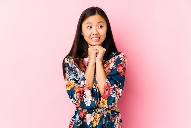 Une jeune femme chinoise portant un pyjama kimono isolé garde les mains sous le menton, regarde joyeusement de côté.