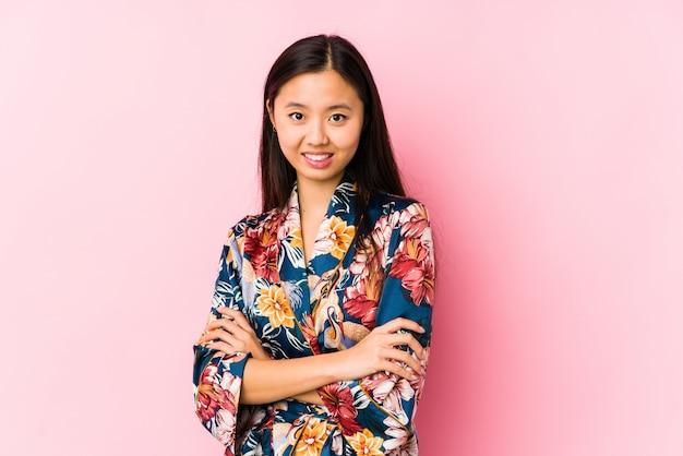 Jeune femme chinoise portant un pyjama kimono isolé qui se sent confiant, croisant les bras avec détermination.